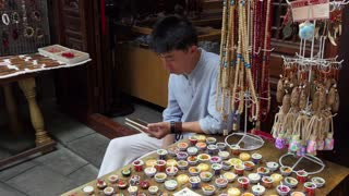 Chinese man selling souvenirs, gifts, presents at market in Jinli old pedestrian street or Jin Li ancient street in Chengdu, Sichuan, China, Asia