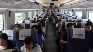 Chinese people traveling on bullet train between Shanghai and Suzhou in China, Asia. Modern railway transportation, fast travel, travelers and Asian commuters