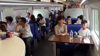 Chinese people traveling on high speed bullet train between Shanghai and Suzhou in China, Asia. Modern railway transportation, fast travel, travelers and Asian commuters in dining or restaurant car
