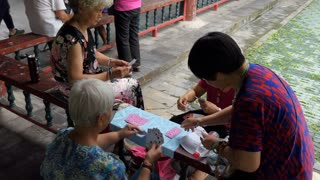 Chinese women playing cards game in Beijing, China, Asia. Female friends having fun with leisure activity outdoors