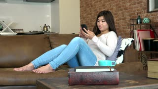 College student texting with mobile phone and smiling. Asian woman on couch at home. Pretty Japanese girl using smartphone for text message, internet and email. Happy people using technology for fun