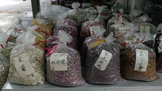 Dried plants and herbs for tea preparation in a small shop at local market in Gulin, China. Traditional culture in Asia