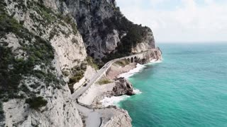 Drone flying between Noli and Varigotti, Liguria, Italy. Aerial view of Northern Italian coast with cars driving on SS1 Aurelia road