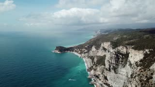 Drone flying between Noli and Varigotti, Liguria, Italy. Aerial view of Northern Italian coast with landscape, sea, mountains and road seen from the sky