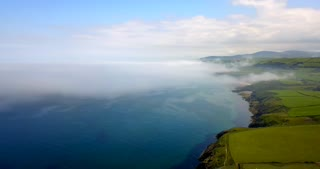 Drone flying in the sky over the coast near Peel on the Isle of Man. Aerial view of traditional British landscape with sudden fog and mist arriving from the sea and changing the weather conditions