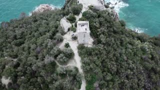 Drone flying over Baia dei Saraceni in Varigotti, Liguria, Italy. Aerial view of charming Italian sea village and old monument seen from the sky