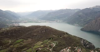 Drone flying over Lake Endine, Lombardy, Italy. Aerial view of charming Italian villages seen from the sky, with the mountains in the background