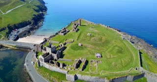 Drone flying over Peel Castle on Isle of Man, landmark building in Peel on the Isle of Man, originally constructed by Vikings. Aerial view of charming sea village and old monument seen from the sky