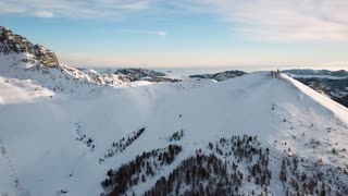 Drone flying over Piani di Bobbio near Lake Como, Northern Italy. Aerial view of the Italian Alps seen from the sky, mountains covered with snow and ski resort