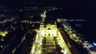 Drone flying over Pietra Ligure, Liguria, Italy. Aerial view of charming Italian sea town and church seen from the sky at night