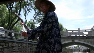 Elderly Chinese man rowing boat in Suzhou, China, Asia. Scenic and historical boat ride for tourists along the city canals