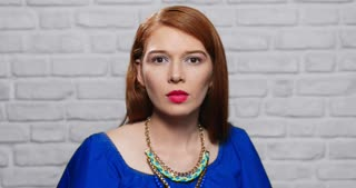 Facial Expressions Of Young Redhead Woman On Brick Wall