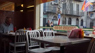 Fast food restaurant at the intersection of Bourbon and Dumaine, streets of the French Quarter in New Orleans, Louisiana, United States of America. American man eating burger and fries for dinner