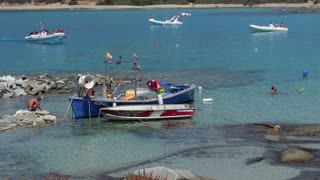 Fishing boat and people on holidays in Italy, tourists with dinghy on vacation. Italian coast in Sardinia on Mediterranean Sea. Crystal clear waters in Punta Molentis, Villasimius, Sardegna, Italia
