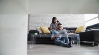 Girl Massaging Boyfriend On Sofa At Home
