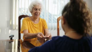 Grandchild And Grandma Playing Magic Tricks With Cards At Home