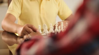 Grandfather Playing Chess Board Game With Grandson At Home