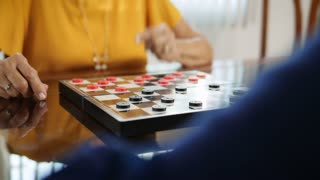Grandmother Playing Checkers Board Game With Granddaughter At Home