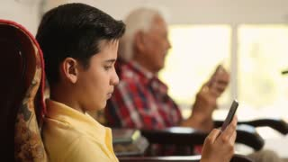Grandpa And Grandson Using Mobile Phone For Internet