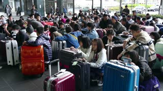 Group of Japanese students with suitcases, luggage, bags and baggage waiting at Kyoto JR Railway Station in Kyoto, Japan, Asia