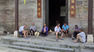 Group of senior Chinese men relaxing, talking and smoking in Jiuxian village, Yangshuo County, Guangxi, China, Asia. Old friends having fun with leisure activity