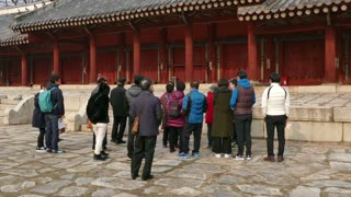 Group of tourists with guide visiting Jeongjeon, the main hall of Jongmyo, a Confucian shrine, Korean monument, tourist spot, UNESCO World Heritage Site in Seoul, South Korea, Asia