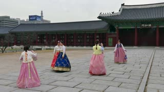 Happy girls wearing hanbok, young women with traditional Korean dress at Gyeongbokgung Palace, monument. Seoul, South Korea, Asia