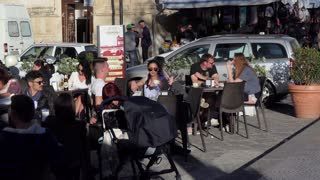 Happy tourists and Italian people enjoying a warm afternoon sitting outdoor in a bar on the street. Syracuse, Siracusa, Sicily, Italy