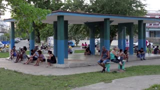 Havana, Cuba. Cuban people using mobile telephone, cell phone, smartphone and ipad digital tablet for internet, social media, network and email. Wireless wifi technology in city park