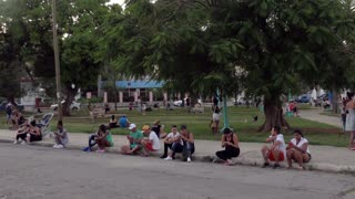 Havana, Cuba. Hispanic people using mobile telephones, cell phones, smartphones and ipad digital tablet for internet, social media and email. Wireless wi-fi technology in city park for Cuban youth