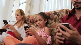 Hispanic Family Laughing Smiling Looking At Picture On Smartphone Telephone