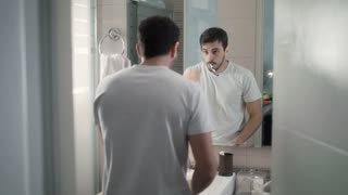 Hispanic Man Brushing Teeth In Bathroom For Morning Routine