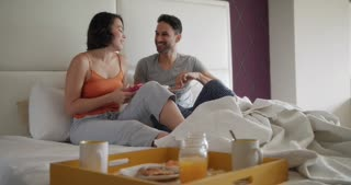 Husband And Wife Eating Breakfast In Bed Using Phone