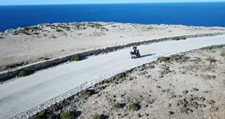 Italian couple riding scooter on the road in the island of Lampedusa, Italy during summer vacation with Mediterranean sea in background