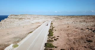 Italian people riding moped on the road in the island of Lampedusa, Italy during summer holiday with Mediterranean sea in background