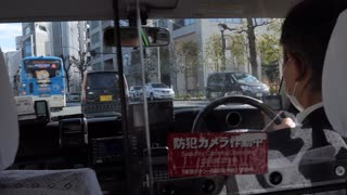 Japanese man driving local taxi in Tokyo, Japan, Asia. View of the car interior with cab driver through traffic, street, cars, road