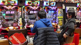 Japanese men playing pachinko, lottery, arcade game, videogames, video games, gambling, slot machines in Asian casino. Tokyo, Japan, Asia