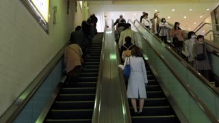 Japanese people and commuters on escalator at Shinjuku JR train station in Tokyo, Japan, Asia during morning rush hour