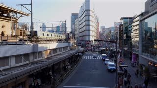 Japanese people walking, trains on railway and street traffic with cars near Ueno JR Station in Tokyo, Japan, Asia