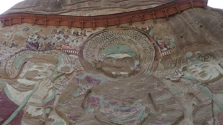 Lashao temple or La Shao Si with giant 30-meter Buddha carved into rock at Luomen, Gansu, China, Asia. Chinese remote site with old Buddhist statue, art, architecture, temples. Monument with painting