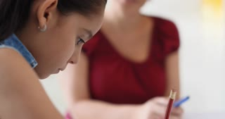 Latina Mom Helping Daughter Doing School Homework At Home