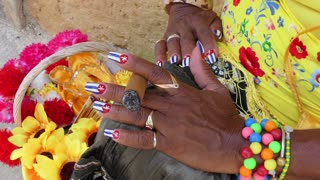 Latina woman smoking cigar in Havana, Cuba. Hispanic black lady and tobacco smoke, Caribbean folklore. Closeup of hand holding cigar with Cuban flags painted on fingernails
