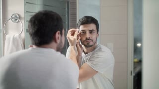 Latino Man Trimming Eyebrow For Body Care at Home