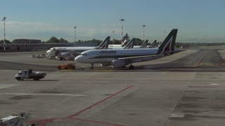 Linate International City Airport, Milan, Italy, Europe. Passenger terminal with Alitalia airplane, plane, jet, aircraft going to runway for take-off. Italian air transportation travel, Milano, Italia