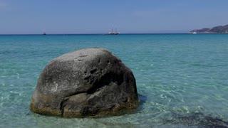 Lone rock in Campulongu beach near Villasimius in Sardegna, Italia. Natural landscape in Italy. Italian coast in Sardinia on Mediterranean Sea, with sailing boat