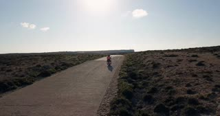 Man and woman riding motorcycle on the street in the island of Lampedusa, Italy during summer holidays with Mediterranean sea in background