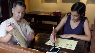Man teaching woman how to write Chinese characters at calligraphy class. Student learning Chinese writing with brush, ink, and paper and teacher helping her. School, education, culture, creativity