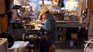Man working as artisan in souvenir shop and painting leather belt. American cowboy at work in traditional Western store in Fort Worth, Texas, United States of America
