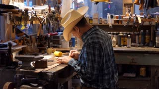 Man working as artisan in souvenir shop and painting leather belt. American cowboy at work in traditional Western store in Fort Worth, Texas, USA