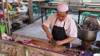 Man working as cook preparing traditional Chinese street food in Lanzhou, Gansu province, China, Asia. Market with stalls and shops selling Asian food. People at work in restaurant kitchen